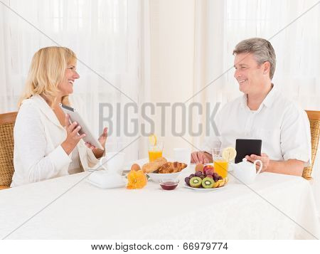 Happy Mature Healthy Couple Using Tablets And Ebook Ereaders At Breakfast