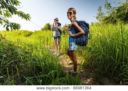 Two ladies hikers with backpacks walking on a green lush meadow