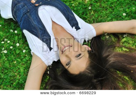 Teenager Lying In Grass With Flowers