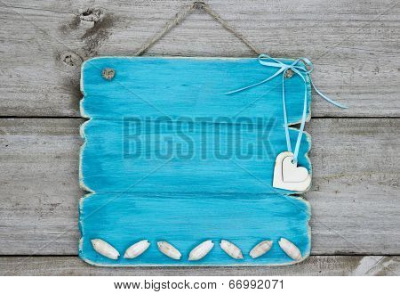 Blank teal blue sign with seashells and hearts hanging on rustic wooden background