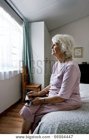 A lonely senior widow sitting on her bed feeling sad