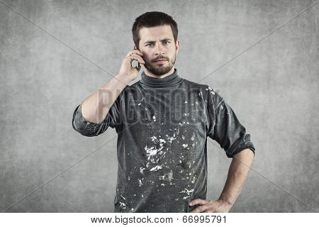 Young Man In Working Clothes Talking On The Phone