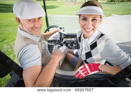 Golfing couple smiling at camera in their golf buggy on a sunny day at the golf course