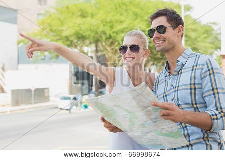 Young tourist couple consulting the map and pointing on a sunny day in the city