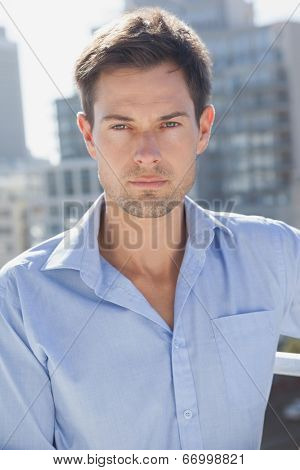 Handsome man frowning at camera on his balcony on a sunny day