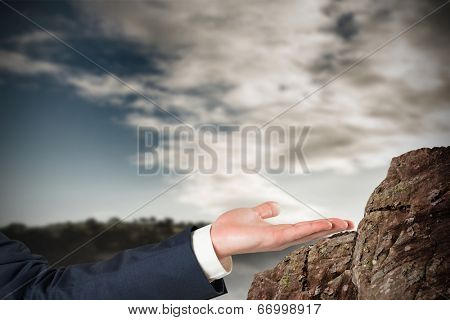 Hand presenting against large rock overlooking vast forest