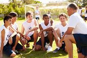 stock photo of 6 year old  - Coach Giving Team Talk To Male High School Soccer Team - JPG