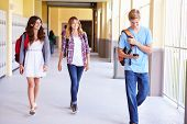 picture of 16 year old  - High School Students Walking In Hallway Using Mobile Phone - JPG