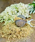picture of meadowsweet  - Metal sieve with dried flowers of meadowsweet a bouquet of fresh flowers of meadowsweet on a wooden boards background - JPG