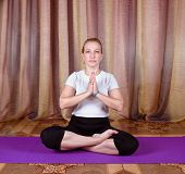 foto of samadhi  - Woman yogi sitting in yoga posture on a purple mat - JPG