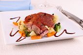 stock photo of duck breast  - Roasted duck breast vegetables with black sauce close up - JPG