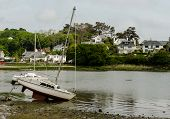 picture of tide  - Small yacht left high and dry by the receding tide - JPG