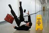 stock photo of hazardous  - Senior businessman falling near caution sign in hallway - JPG