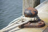picture of bollard  - A bollard in a harbor with a thick rope to fasten a ship - JPG