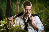 stock photo of machete  - Attractive confident businessman with machete walking in the jungle - JPG