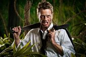 stock photo of machete  - Confident strong businessman dealing with jungle dangers holding a machete - JPG