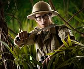 pic of machete  - Watchful young adventurer holding a machete walking through the jungle - JPG