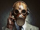 pic of gas mask  - Man wearing vintage gas mask and headphones listening to music - JPG