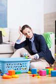 pic of superwoman  - Tired woman cleaning up room from kids toys - JPG