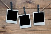 stock photo of clotheslines  - empty polaroid photo frames on wooden background - JPG