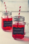 stock photo of mason  - Two raspberry lemonade mason jars with stripe straws - JPG
