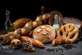image of croissant  - Composition of breads croissants and rolls with milk oil and coffee beans on wooden and black background - JPG