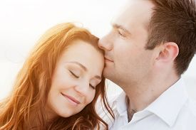 stock photo of forehead  - Young happy couple in love in a romantic moment of man kissing his wife in a forehead on the beach in summer sunshine - JPG