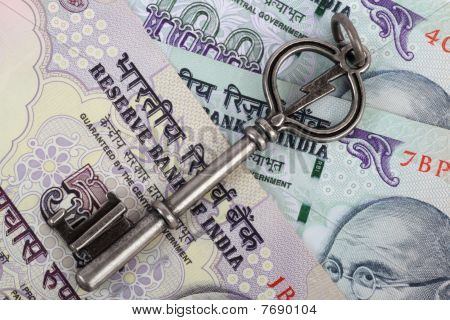 India Currency with an antique key on top