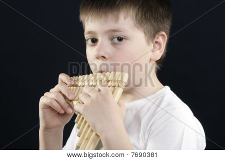 Boy In White Shirt Playing Bamboo Panflute