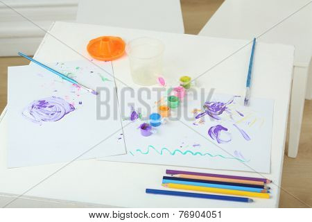 Childrens creativity on the table with paints, brushes and colored pencils