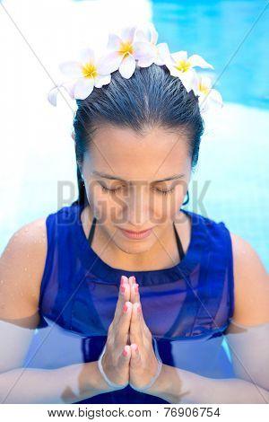 Beautiful woman with frangipani flowers in her hair, praying pose in swimming pool