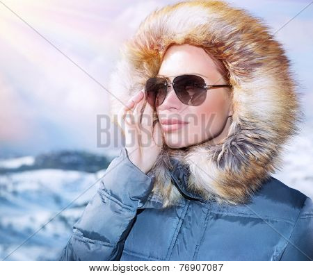 Luxury woman portrait in wintertime, wearing stylish sunglasses and warm coat with furry hood and looking away, winter fashion concept