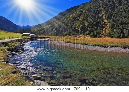 Crystal-clear water shines on the midday sun. Through rather narrow stream will throw the wooden bridge. The Austrian Alps