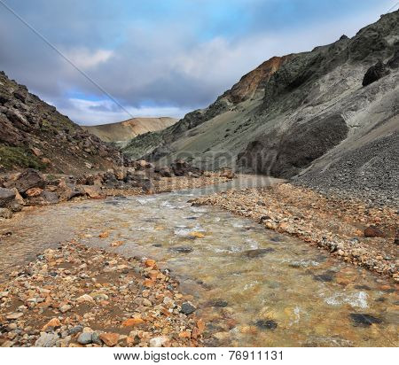 National Park Landmannalaugar in Iceland. Creek in the gorge between the mountains of black volcanic ash