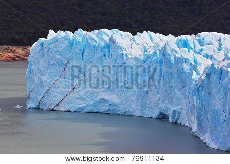 Giant lake Perito Moreno glacier. White-blue ice massif multimeter height rises over the lake