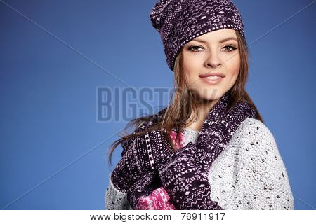 beautiful woman in warm clothing on blue background