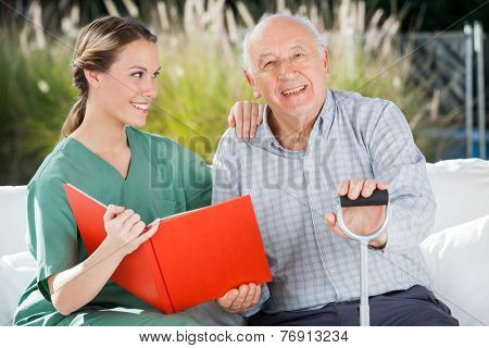 Portrait of happy senior man sitting by female nurse holding book at nursing home