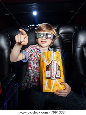 Smiling boy with popcorn paperbag pointing while watching 3D movie in theater