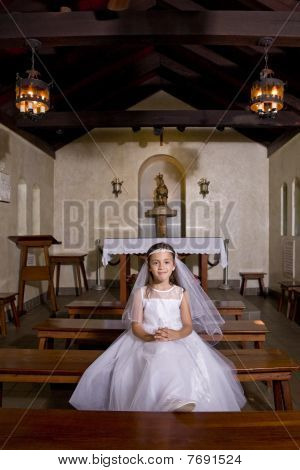 Young Girl In Church Wearing First Communion Dress