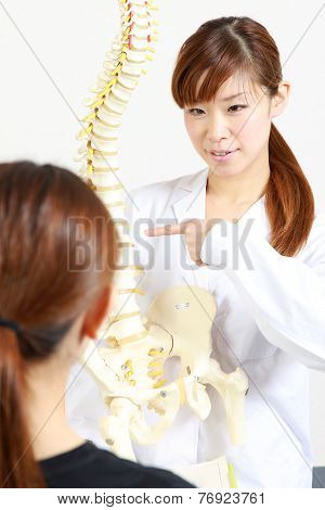 Chiropractor using a plastic model to explain