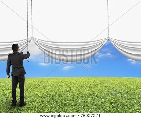 Businessman Pulling Open Blank White Curtain Revealed Natural Sky Grass