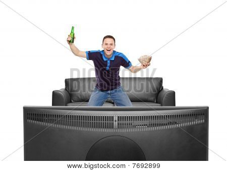 Sport fan with beer bottle and popcorn in his hands watching a match on TV
