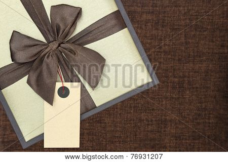 Gift box with ribbon and blank tag on brown background