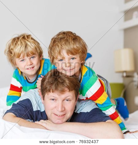 Two Little Sibling Kid Boys And Dad Having Fun In Bed After Sleeping
