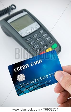 Hand Holding Credit Card. Payment Terminal In Background