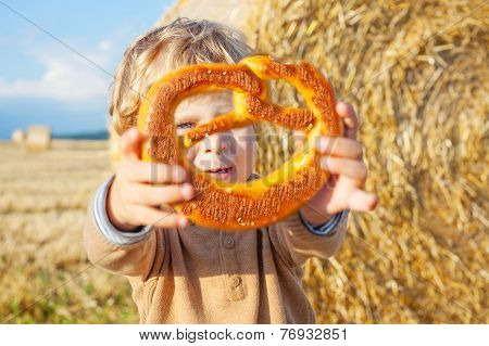Funny Cute Little Kid Boy Eating Pretzel On Late Summer Day On Wheat Field