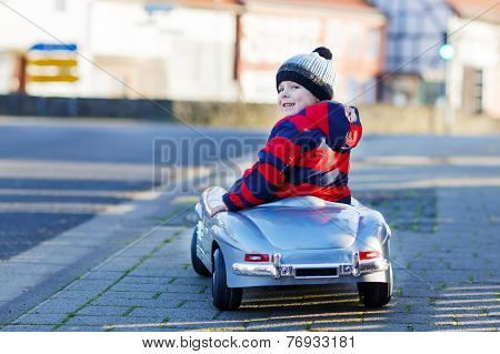 Funny Little Boy Driving Big Toy Car And Having Fun, Outdoors