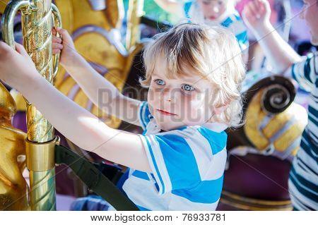 Little Cute Boy During Carousel Ride, Enjoying And Having Fun