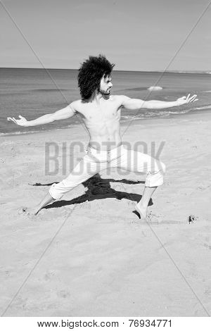 Serious Handsome Man Doing Yoga On The Beach