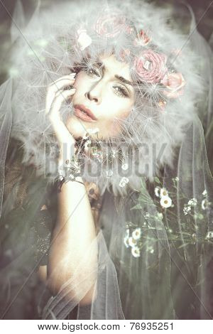 young beautiful  fantasy fairy woman with dandelion around her head on magic meadow